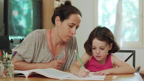 Mother helping her little daughter to prepare homework at home GIF