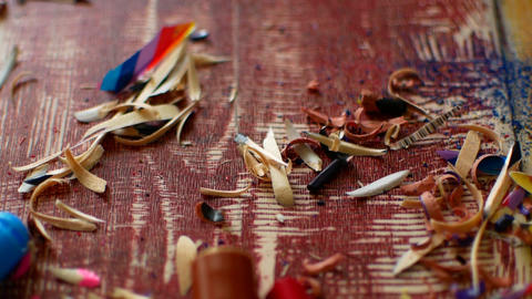 Colored pencils with pencil shavings on wooden background Footage