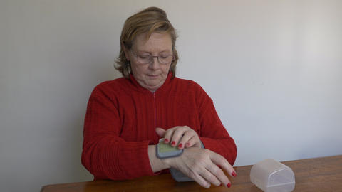 Middle aged woman takes a pressure reading with his wrist monitor Archivo