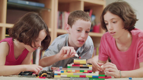 Three kids playing with lego bricks at home Footage