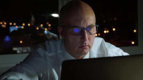 Executive businessman in eyeglasses looking at laptop workig late in evening Footage