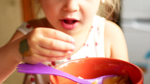 A child eats honey with a spoon from a plastic jar 4k Footage
