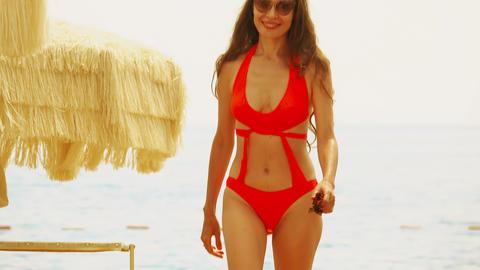 Beautiful young woman in orange bikini walks on the beach GIF