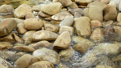 water flows around balanced stones in flowing river Footage