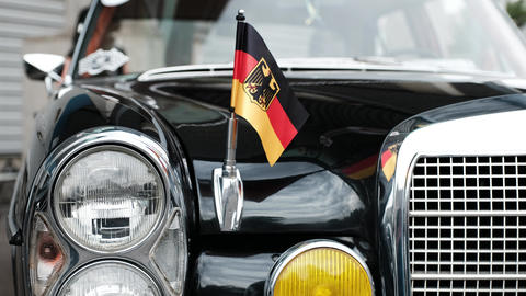 Retro car of black color of German manufacture. The German flag is fixed on a Footage