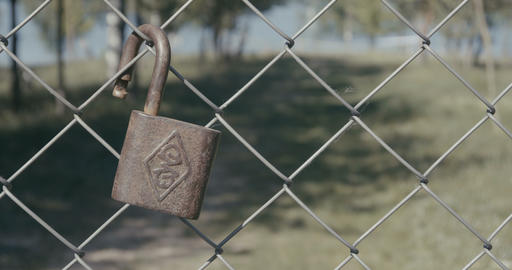 4K - metal lock hanging on a fence in the background of a beautiful landscape ビデオ
