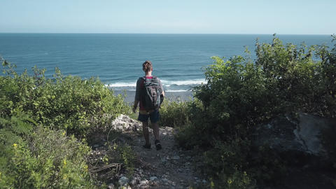 View from above on traveling backpacker admiring ocean view on the cliff Archivo