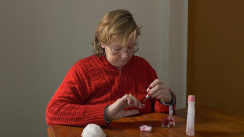 Middle aged woman painting her fingernails Footage