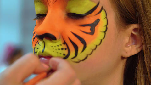 Portrait girl receiving body art on face like tiger. Closeup tiger face aquagrum Live Action