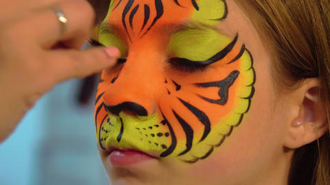 Portrait girl receiving body art on face like tiger.… Stock Video Footage