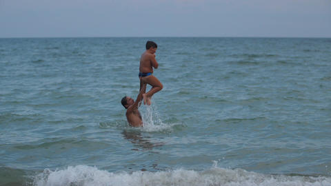 A boy jumps into the water from his father's shoulders Slow motion video Footage