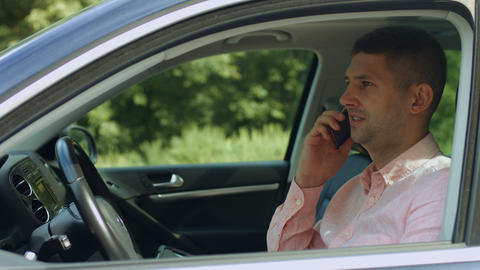 Confident male driver talking on cellphone in car GIF