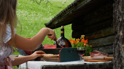 a teenager dressed in a typical Tyrolean dress cuts dry bread with a typical Footage