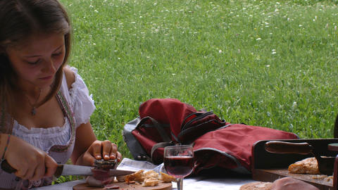 a teenager dressed in a typical Tyrolean dress eats some slices of bacon Footage