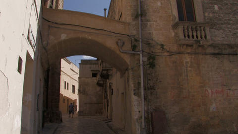 Old woman walking through narrow road Stock Video Footage
