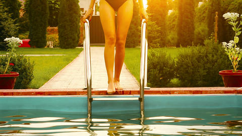 Pretty girl in bikini in the pool at sunset Stock Video Footage
