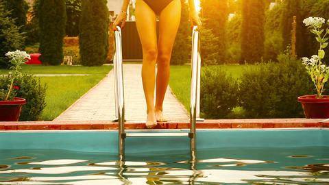 Pretty girl in bikini in the pool at sunset Stock Video Footage