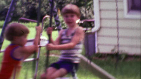 1968: Kids swinging on seesaw style playground lifting up from ground Footage
