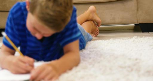 Kid lying on the floor drawing Footage