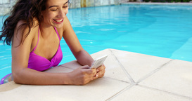 Smiling woman relaxing on pool and using smartphone Live Action