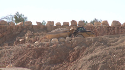 Heavy building bulldozer and dump truck passing on a road in a quarry Footage