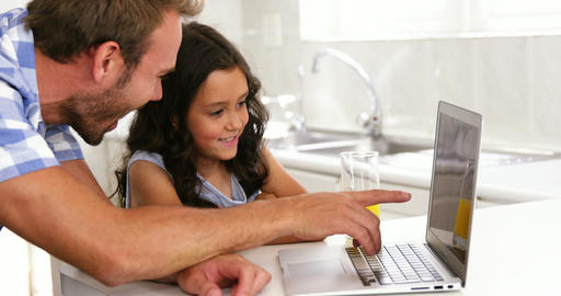 Daughter and father laughing in front of a laptop Live Action
