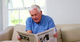 Mature man reading newspapers on sofa Footage