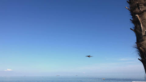 Drone flying over sea. Small drone hovering in a bright blue sky Footage