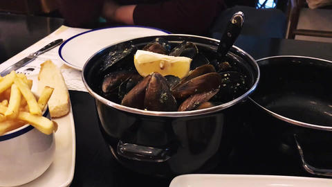Mussels with a cheese sauce served with french fries 영상물