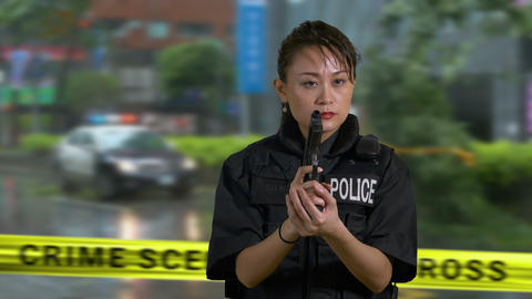 Asian American police officer holds gun looks around crime scene tape GIF