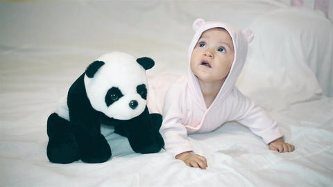 A little girl in a bear costume playing with a Panda on the bed ビデオ