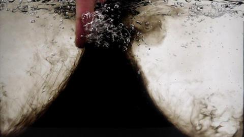 An ink whirlpool from a human finger in an aquarium ビデオ