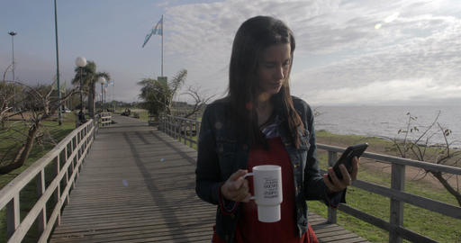 Beautiful woman walking and reading on the phone – 4K Stock Video Footage