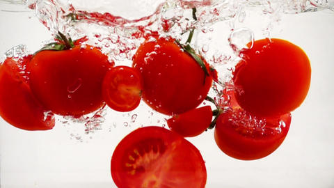 Juicy vegetables tomatoes halves are immersed in water, slow motion close-up 영상물