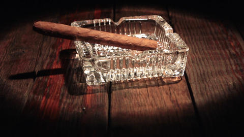 Vertical panorama of a cigar lying in a black ashtray in the beam of light Footage
