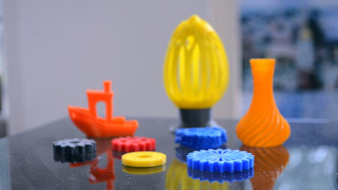 Many bright multi-colored objects printed on 3d printer lie on flat surface ライブ動画