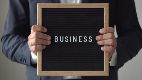 Word Business from Letters on Text Board in Anonymous Businessman Hands GIF
