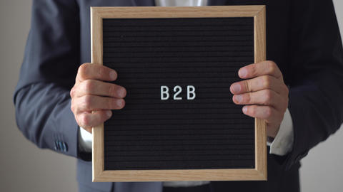 Word B2B from Letters on Text Board in Anonymous Businessman Hands Footage