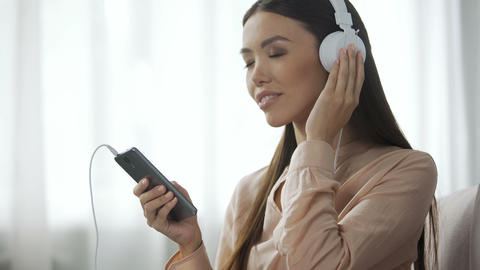 Appealing woman listening music in headphones, loves radio station, enjoyment Live Action