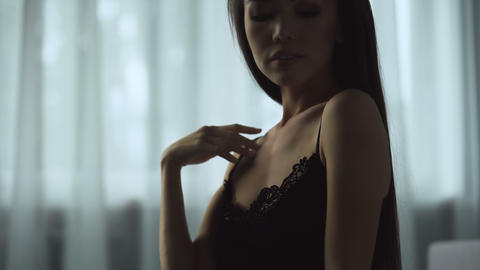 Alluring woman in black lingerie flirting on bed, tender and soft touches Live Action