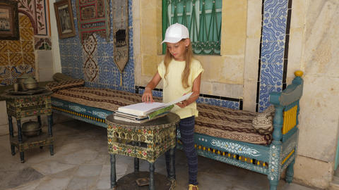 Sousse, Tunisia - June 15, 2018: girl looking ancient book in historical art and Footage