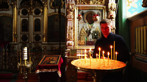 Elets, Russian Federation - April 2, 2018: A man lights a candle and put it in Footage