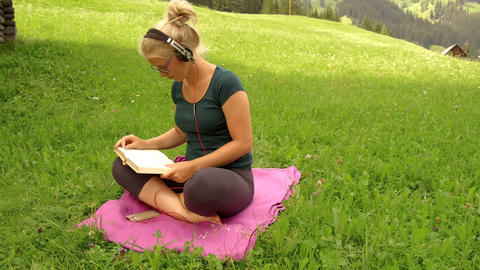 blonde girl reads book on a green grass Footage