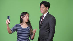 Young handsome Asian businessman and young Asian woman working together Footage