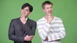 Young handsome Asian businessman and young Scandinavian businessman working Footage