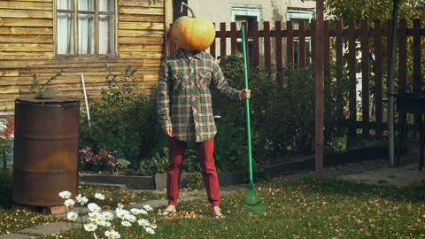 Pumpkinhead person with rake in the garden Footage