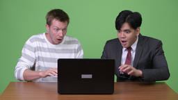 Young Asian businessman and young Scandinavian businessman working together with Footage