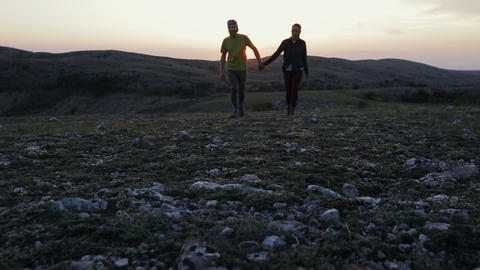Couple holding hands hiking outdoors at romantic sunset.… Stock Video Footage