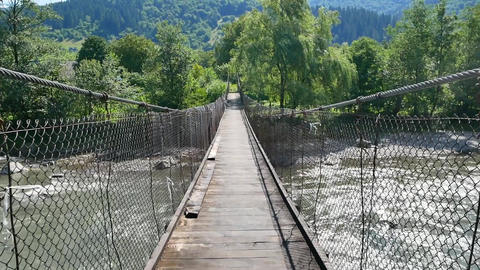 Crossing a river on a small wooden bridge crossing located on a eco path Live Action