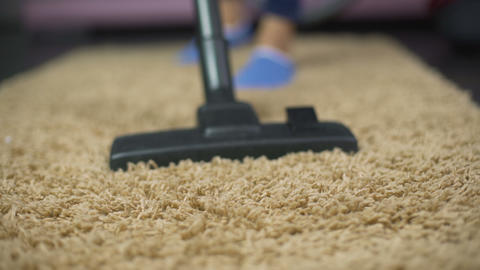 Close-up of vacuum cleaner sweeping dust from expensive rug, household hygiene Footage